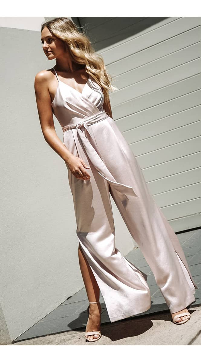 ALL IN ONE This silky blush satin wrap jumpsuit is a dreamy dress alternative. Elongate the wide-leg silhouette with a pair of strappy high heels.